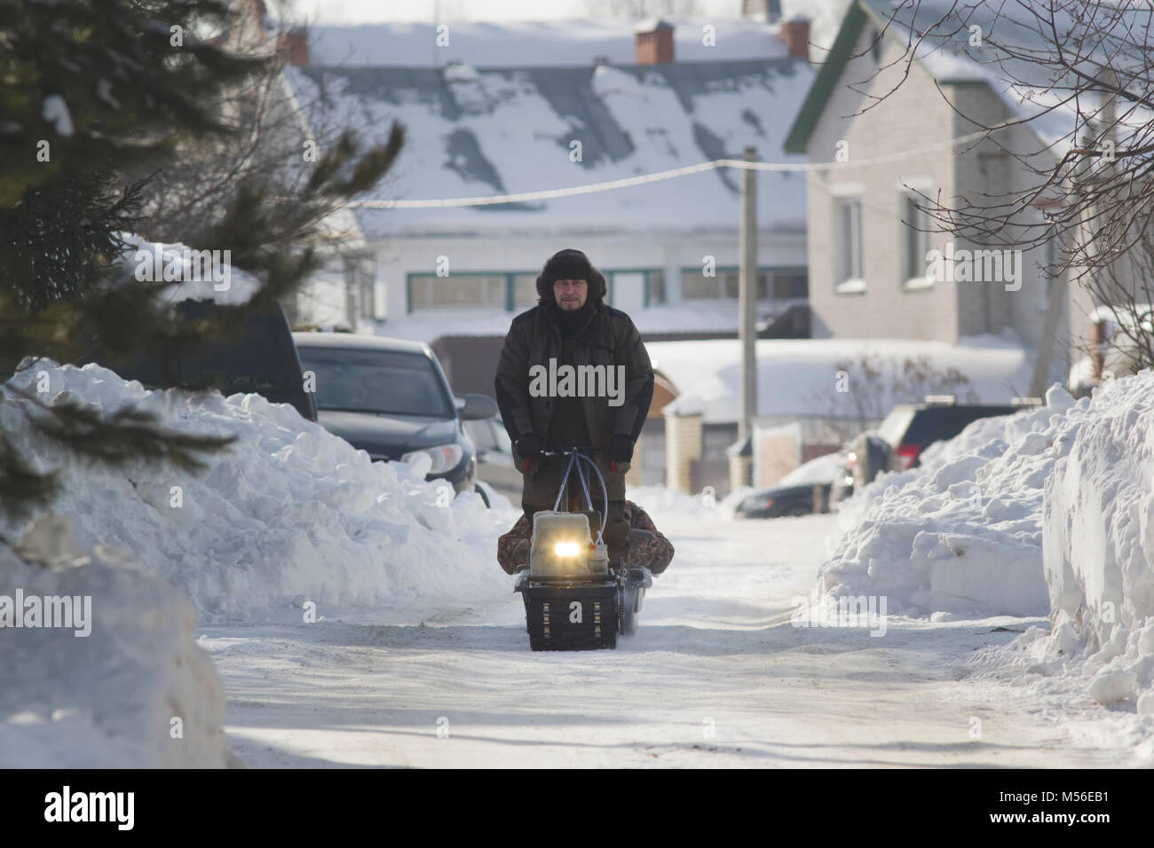 Compact snowmobile - motorcycle towing pulls cargo on snow countryside - Stock Image