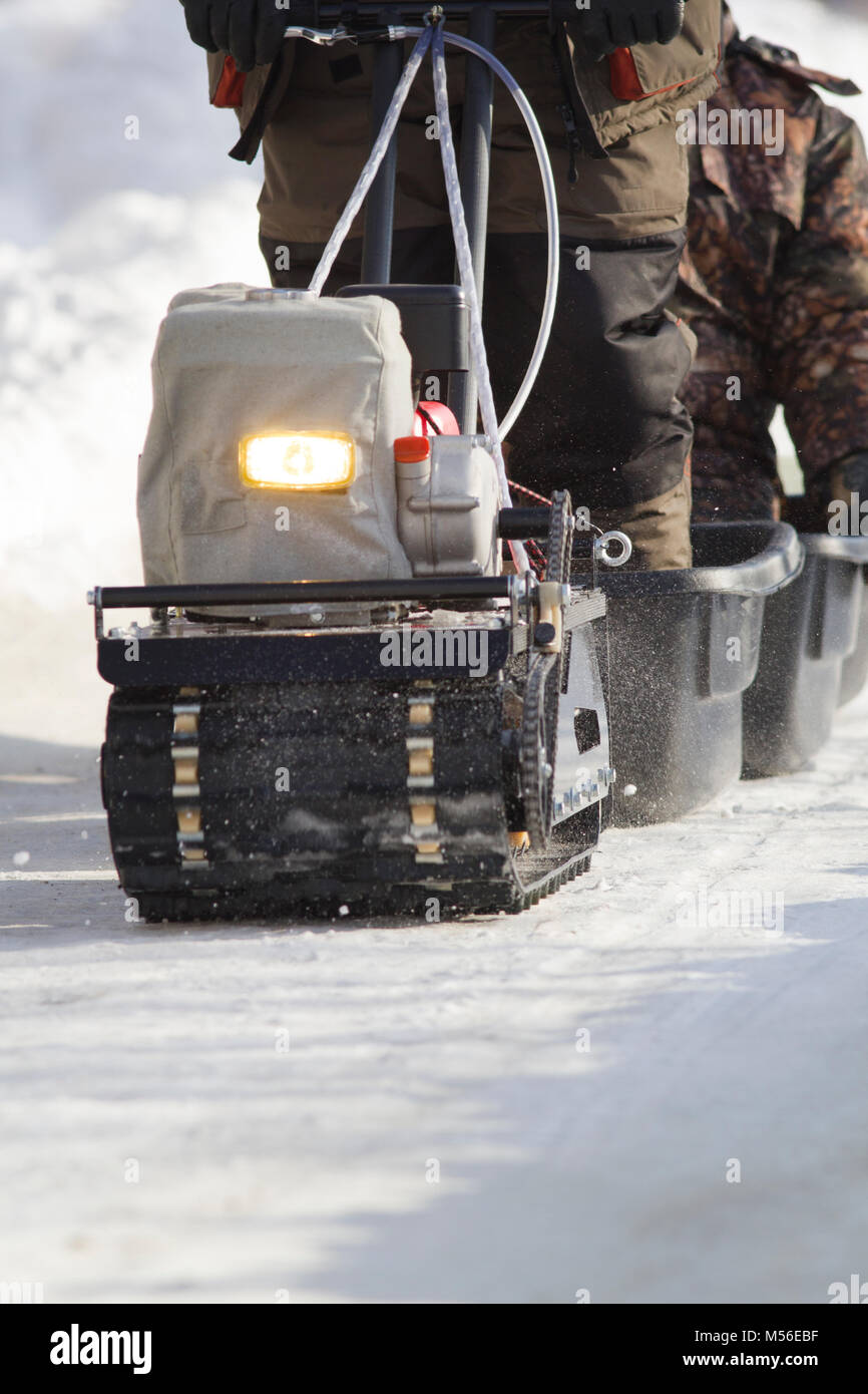 Compact snowmobile close up - motorcycle towing pulls cargo on snow countryside - Stock Image