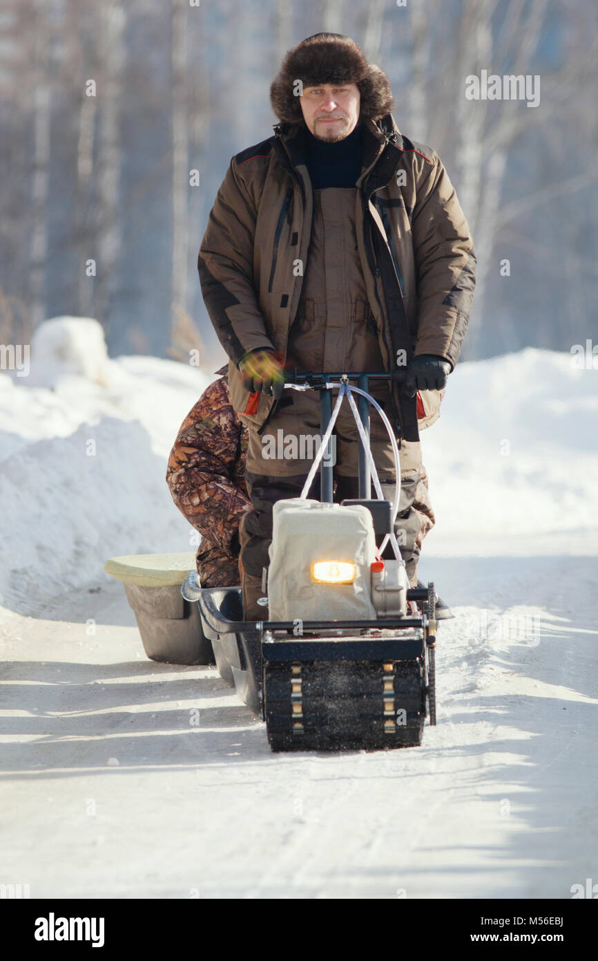 Compact snowmobile for hunting - motorcycle towing pulls cargo on snow countryside - Stock Image