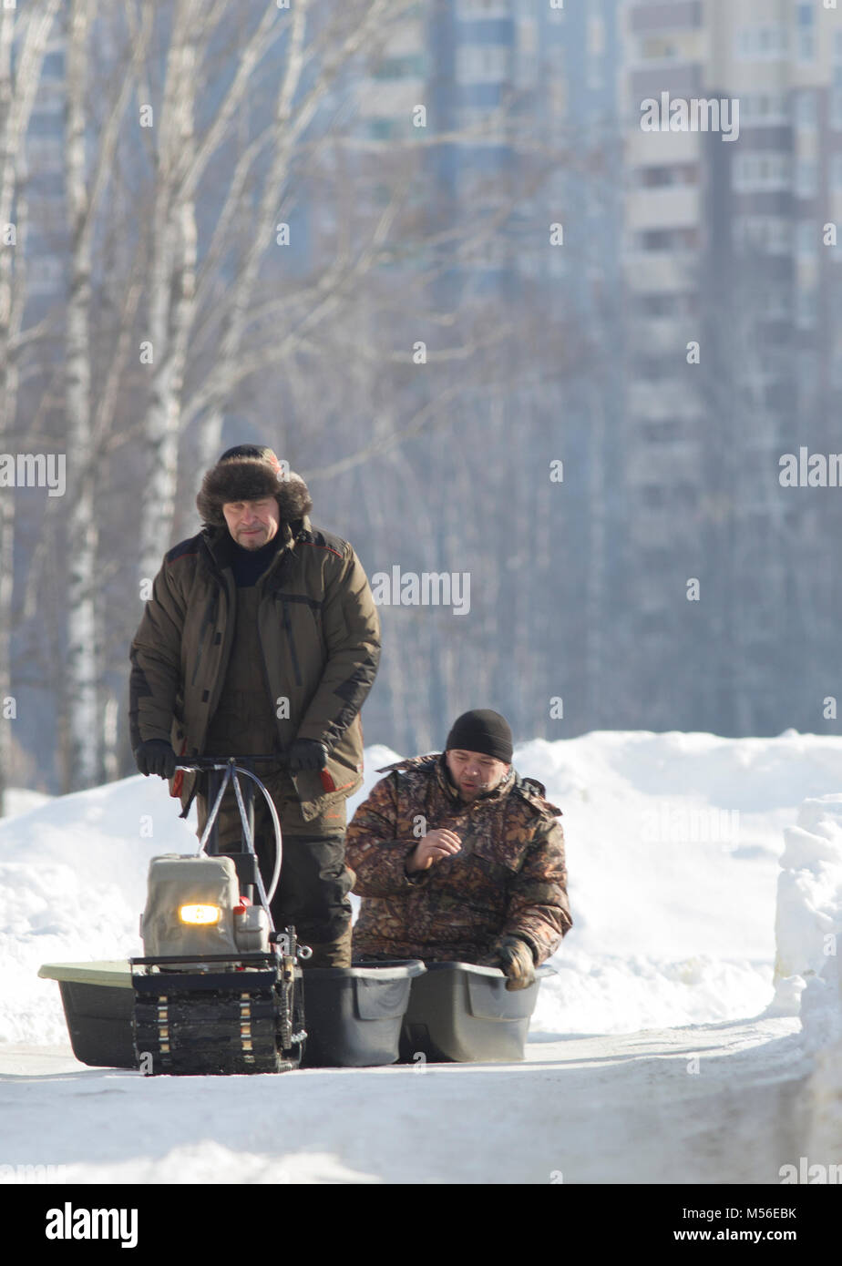 Compact snowmobile for hunting - motorcycle towing pulls two hunters at sunny winter countryside - Stock Image