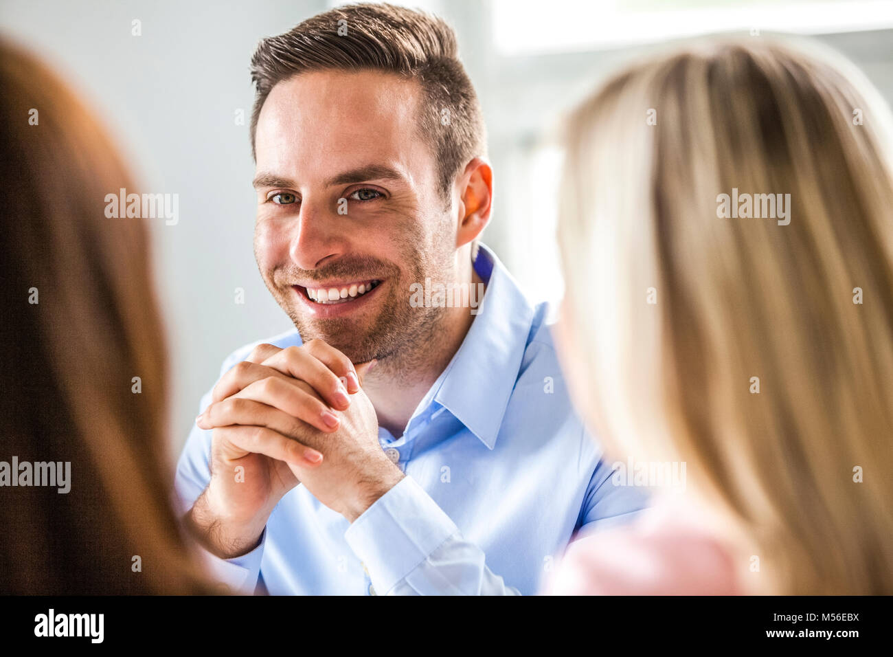 Smiling young businessman with female colleagues in board room - Stock Image