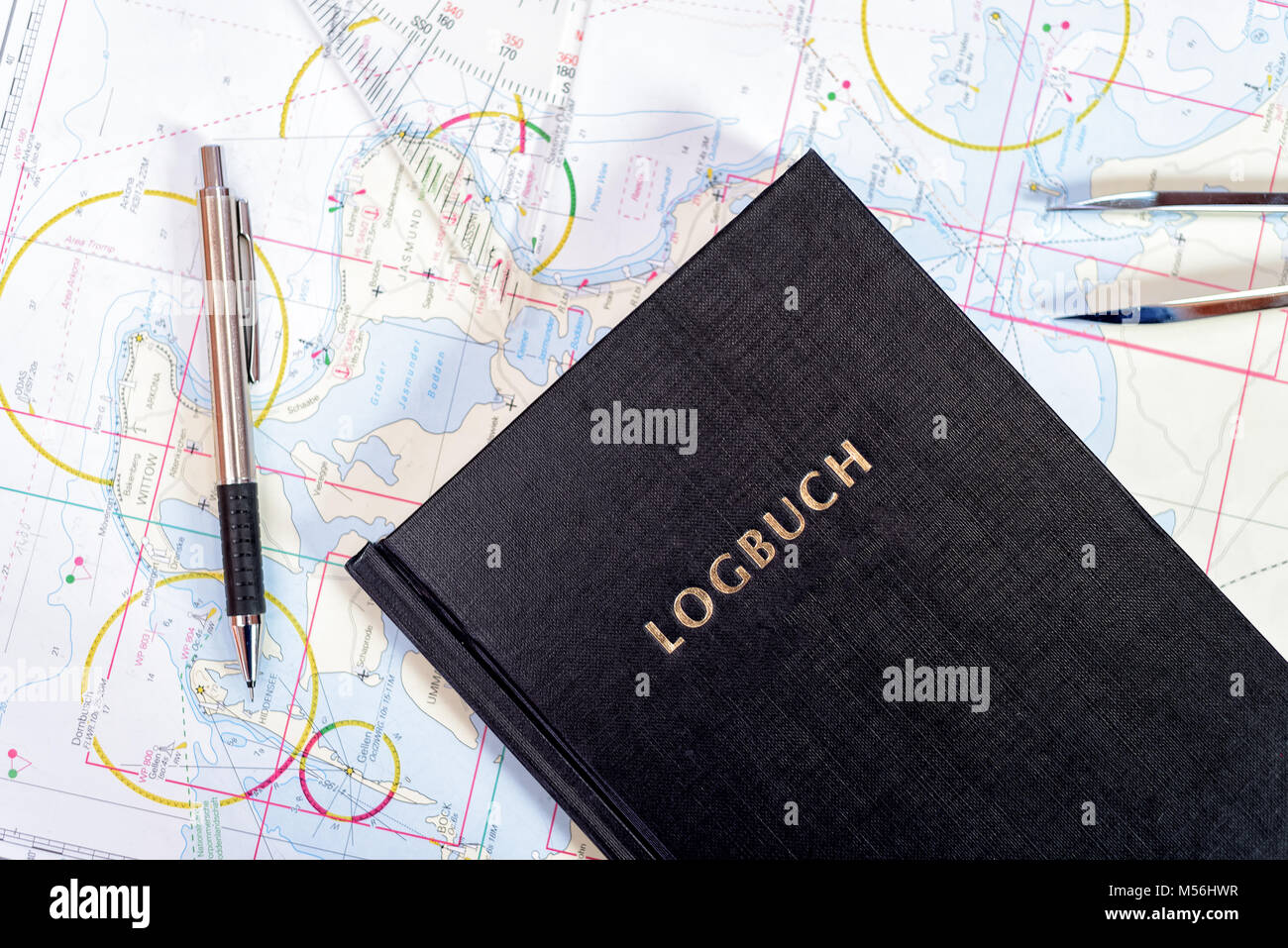 navigation book in the chart room on a sailing yacht - Stock Image