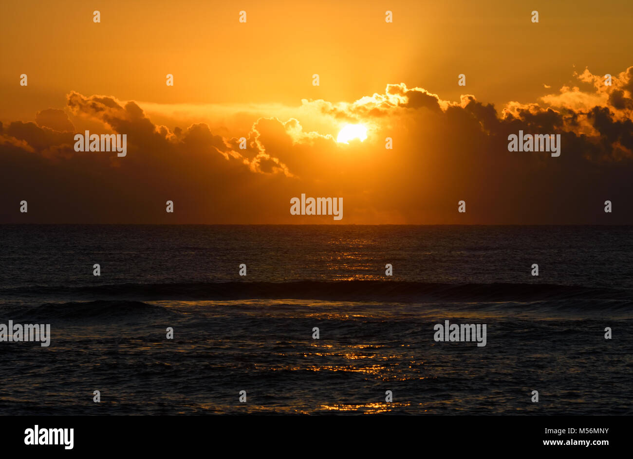 Golden sunrise or sunset over the sea. Sunlight reflects from water waves. - Stock Image
