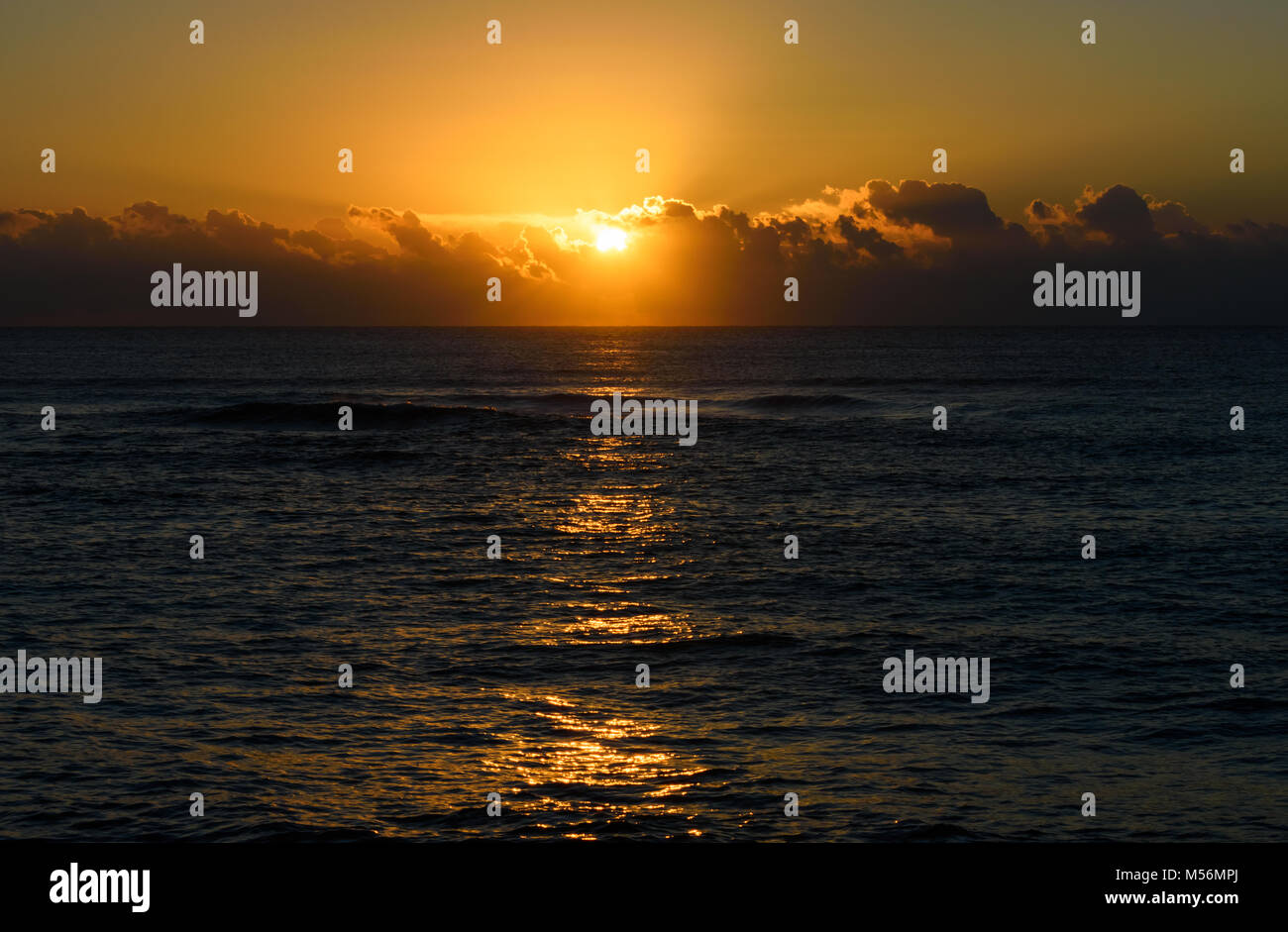 Golden beach sunrise or sunset over the sea. Reflection of the sun on the water. - Stock Image
