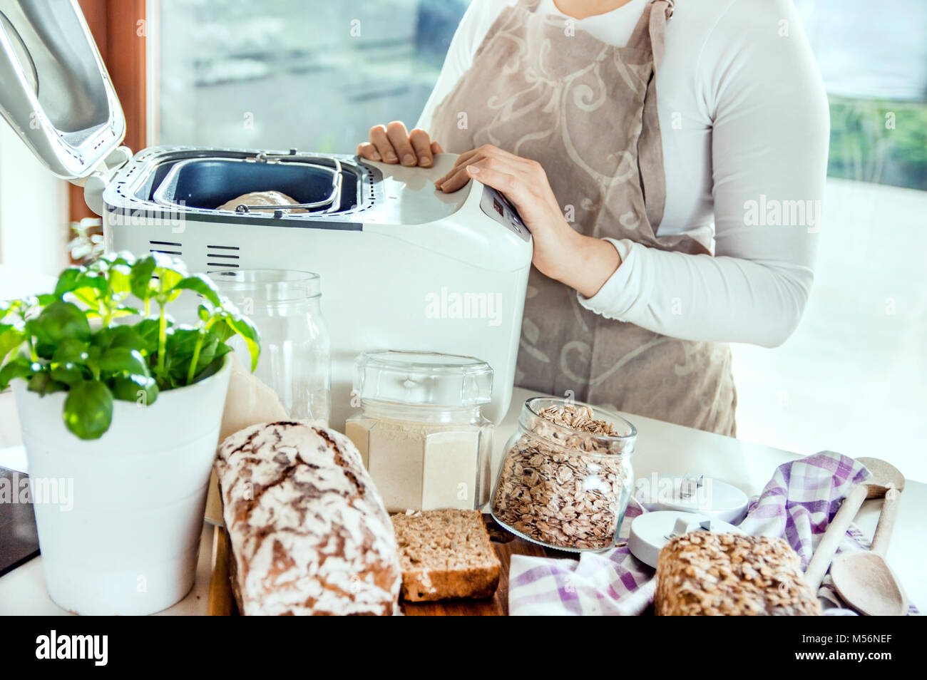 Woman in a modern kitchen among the ingredients for homemade bread prepares a machine for baking. Photo taken in Stock Photo