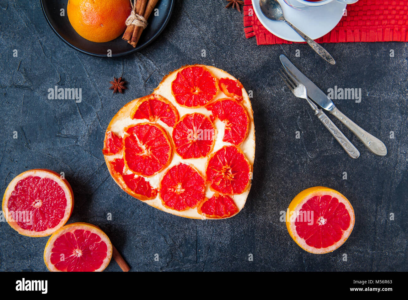 Top view Baked cheesecake with red grapefruit slices in the shape of heart on the black stone background with ingredients - Stock Image