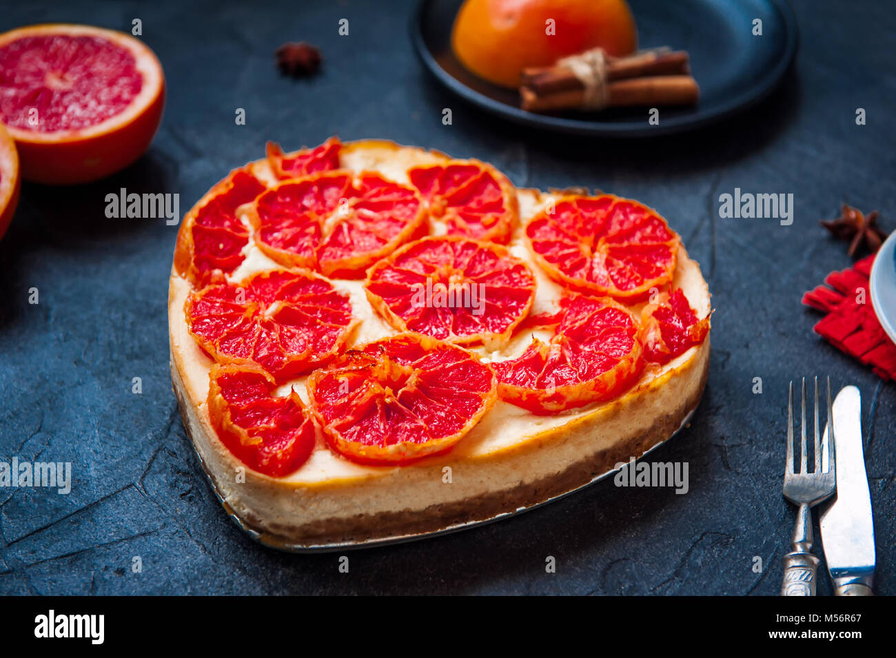 Baked cheesecake with red grapefruit slices in the shape of heart on the black stone background with ingredients - Stock Image