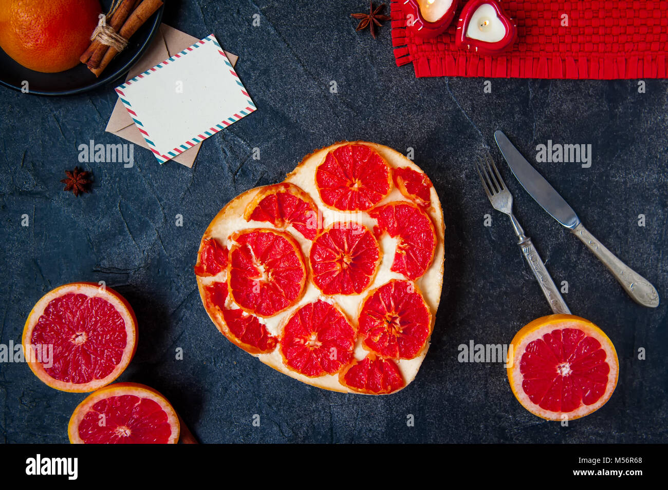 Top view baked cheesecake with red grapefruit slices in the shape of heart on the black stone background, postcard - Stock Image