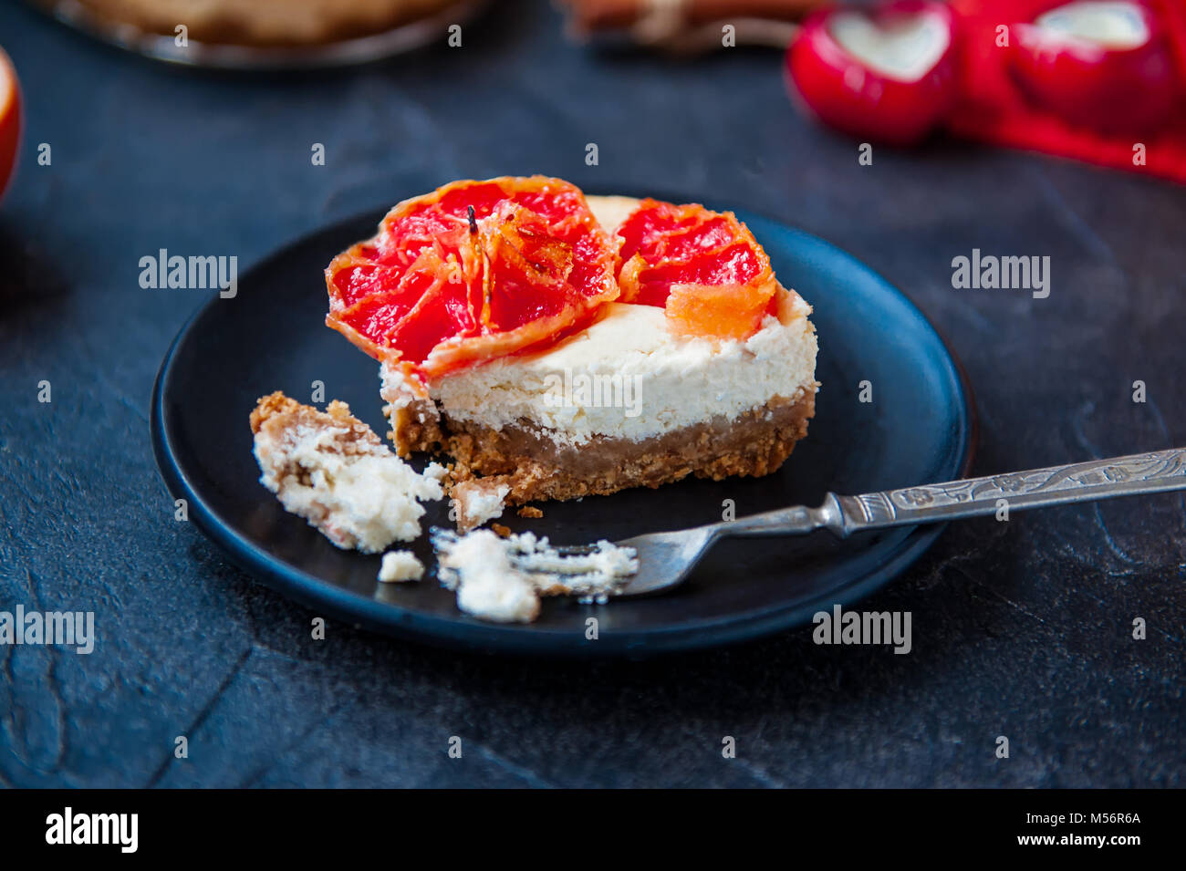 Plate with piece of baked cheesecake with red grapefruit slices and vintage fork on the black stone background with Stock Photo