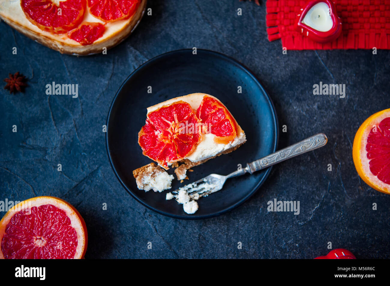 Top view plate with piece of baked cheesecake with red grapefruit slices and vintage fork on the black stone background - Stock Image