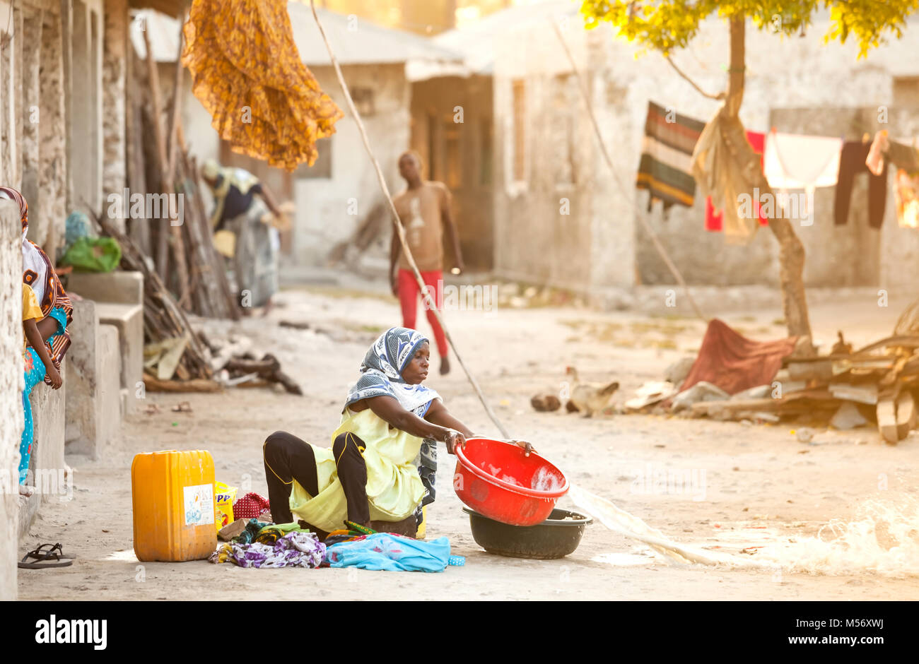 Stone Town, Zanzibar - January 20, 2015: Women throwing out her washing water and sitting on the floor - Stock Image