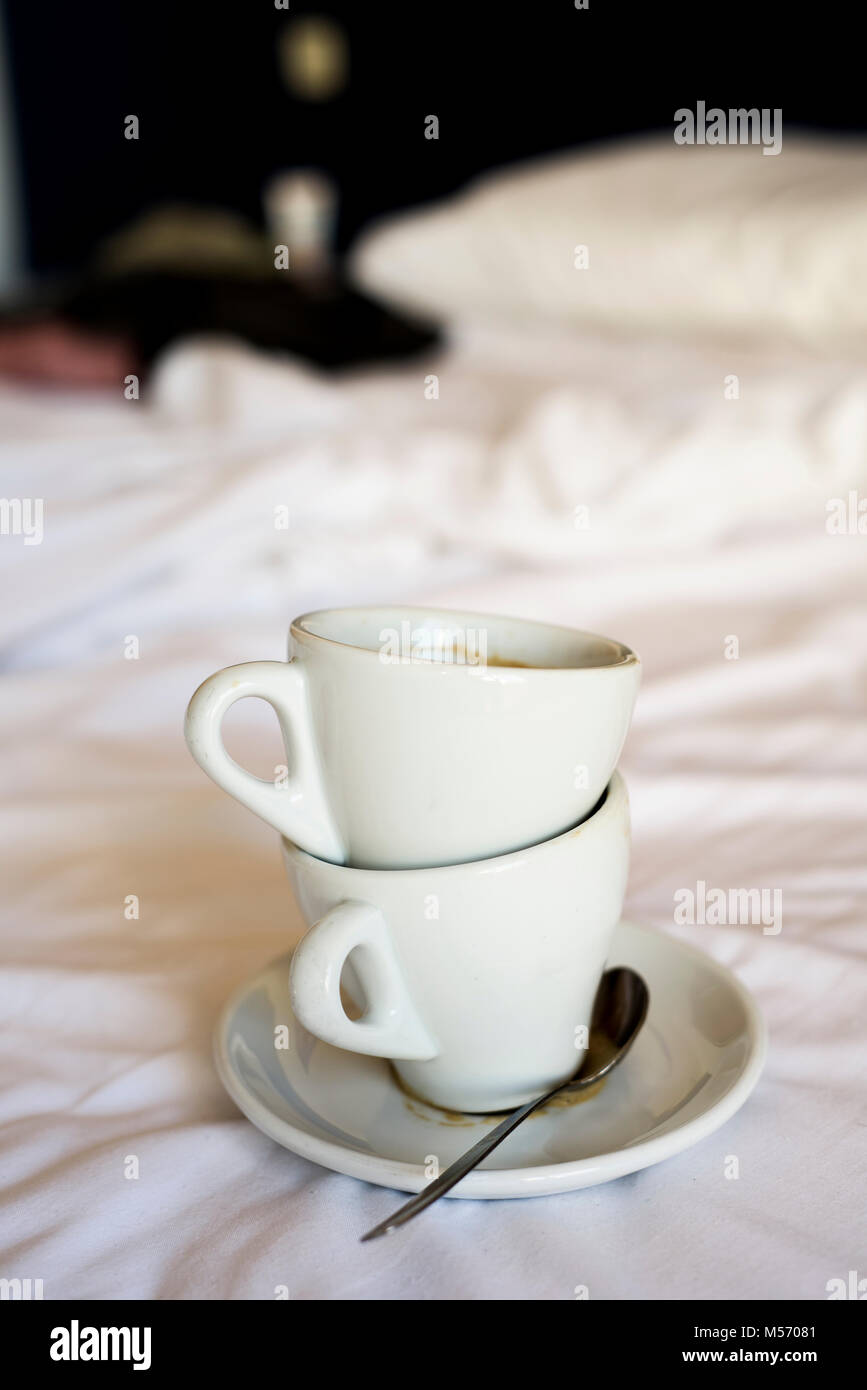 two white ceramic empty cups of coffee on the white sheets of an unmade bed - Stock Image