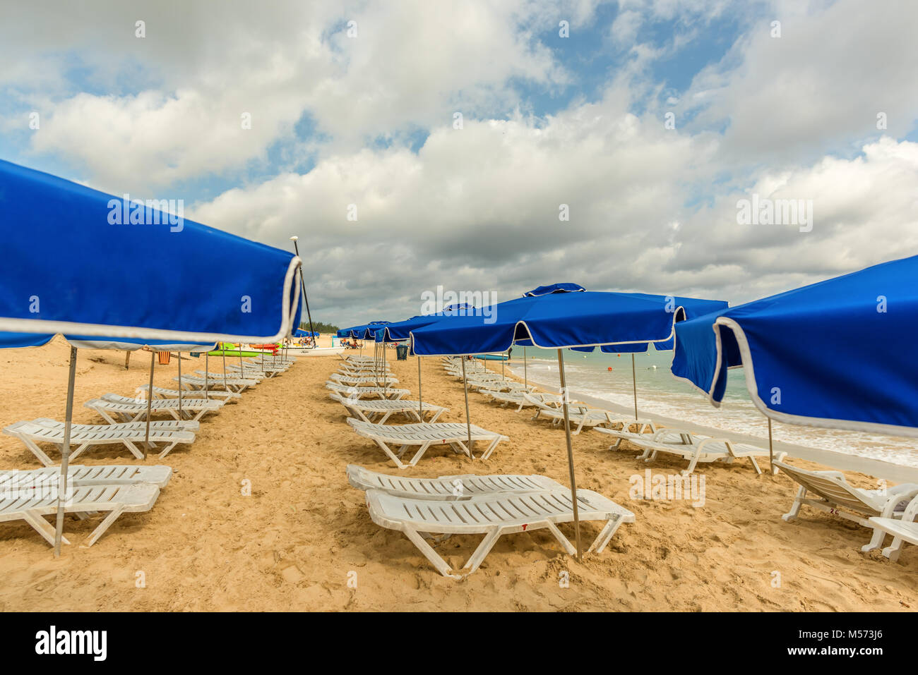white chaise lounges and blue umbrellas stand on a beach in the sand near the ocean with green waves and a blue - Stock Image
