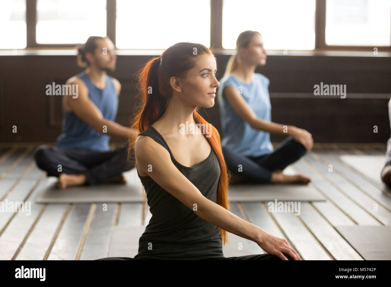 Attractive yogi woman and a Group of people in Matsyendrasana - Stock Image