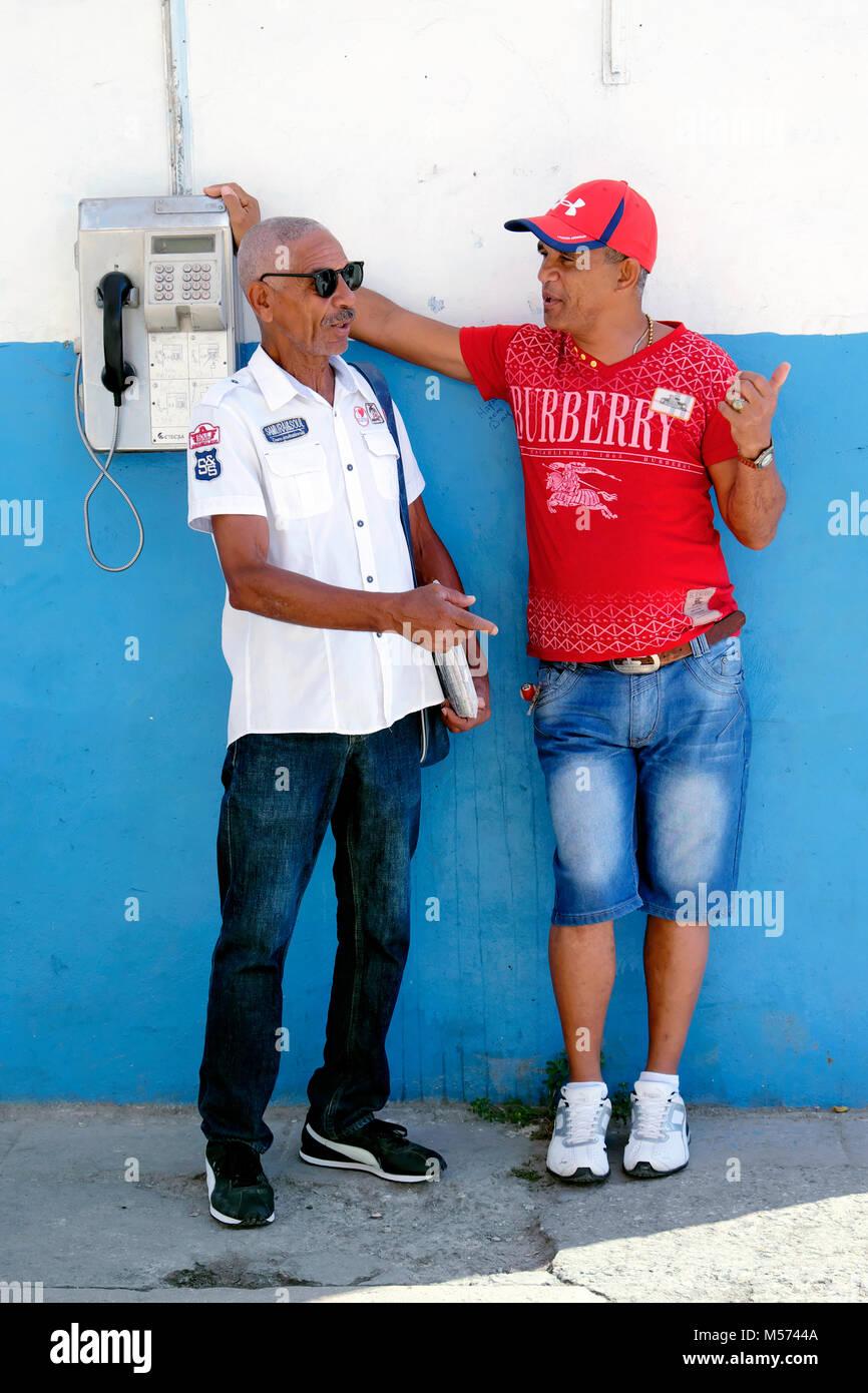 Small talk next to a public coin telephone, Central Havana, Cuba - Stock Image