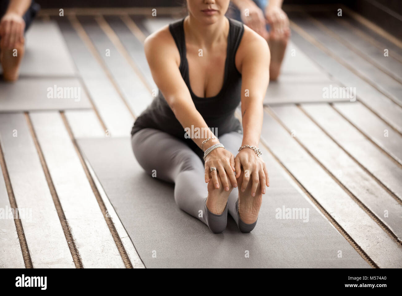 Young sporty woman in paschimottanasana pose - Stock Image