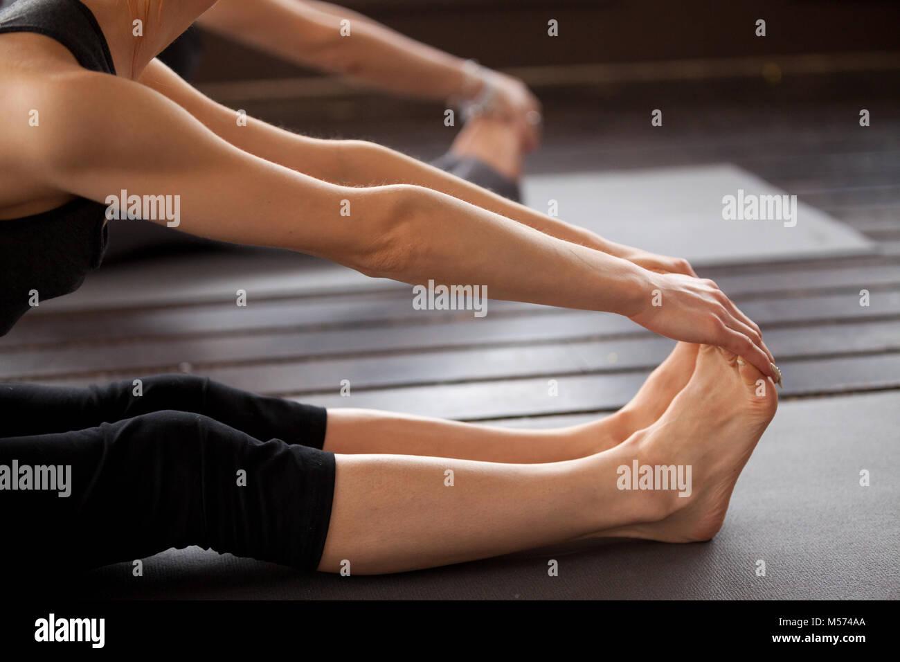 Closeup of yogi woman in paschimottanasana pose - Stock Image