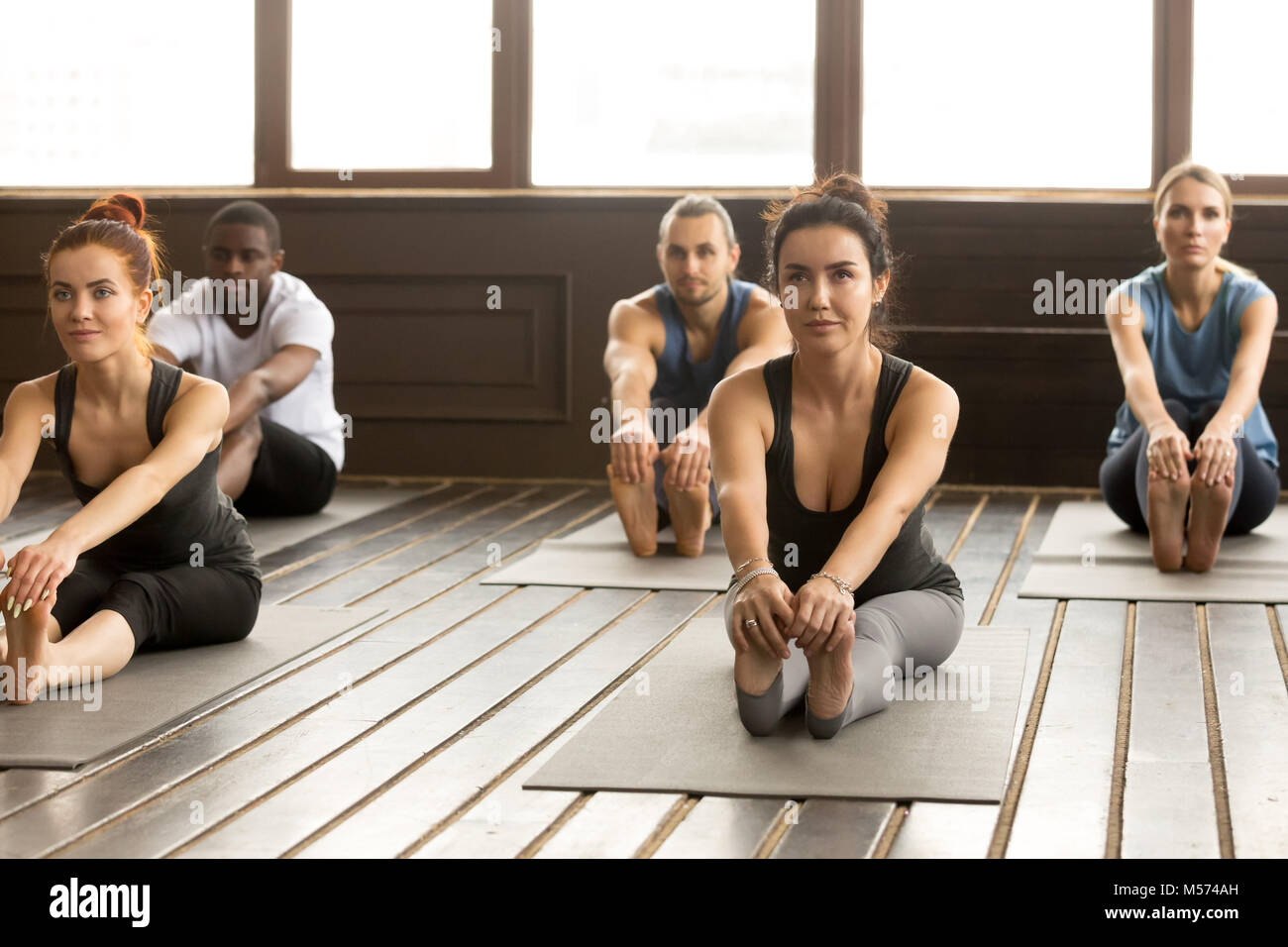 Group of sporty people in paschimottanasana exercise - Stock Image