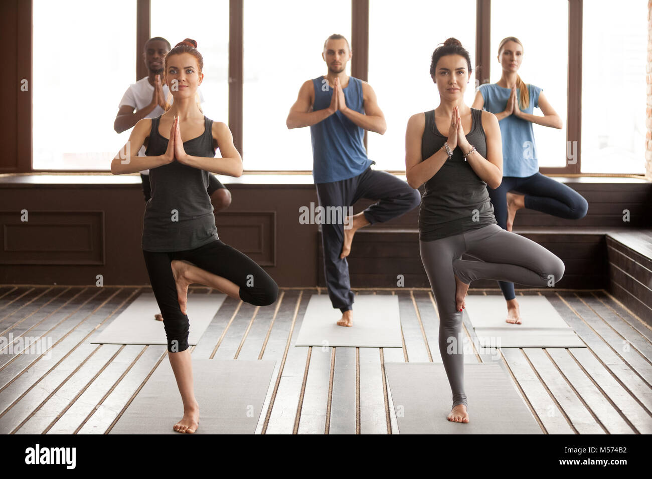 Group of sporty people in Vrksasana pose Stock Photo