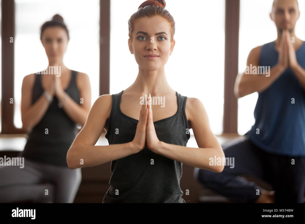 Young smiling attractive woman and a group in Tree pose Stock Photo