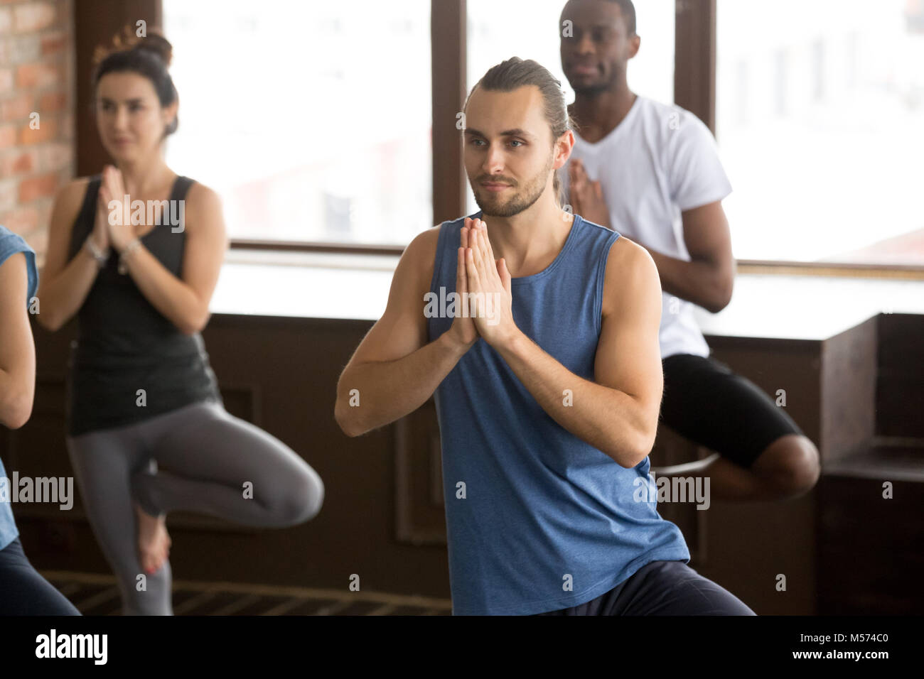 Group of sporty people in Tree pose Stock Photo