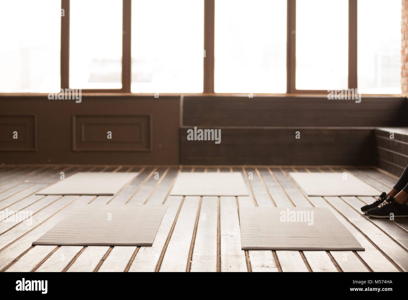 Studio with yoga mats on wooden floor for group training - Stock Image