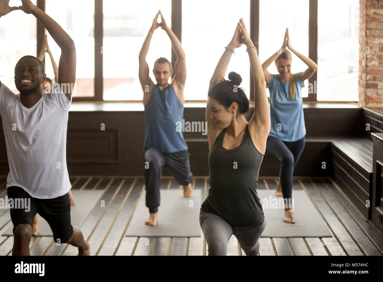 Group yoga in studio, diverse people doing exercises with instru - Stock Image