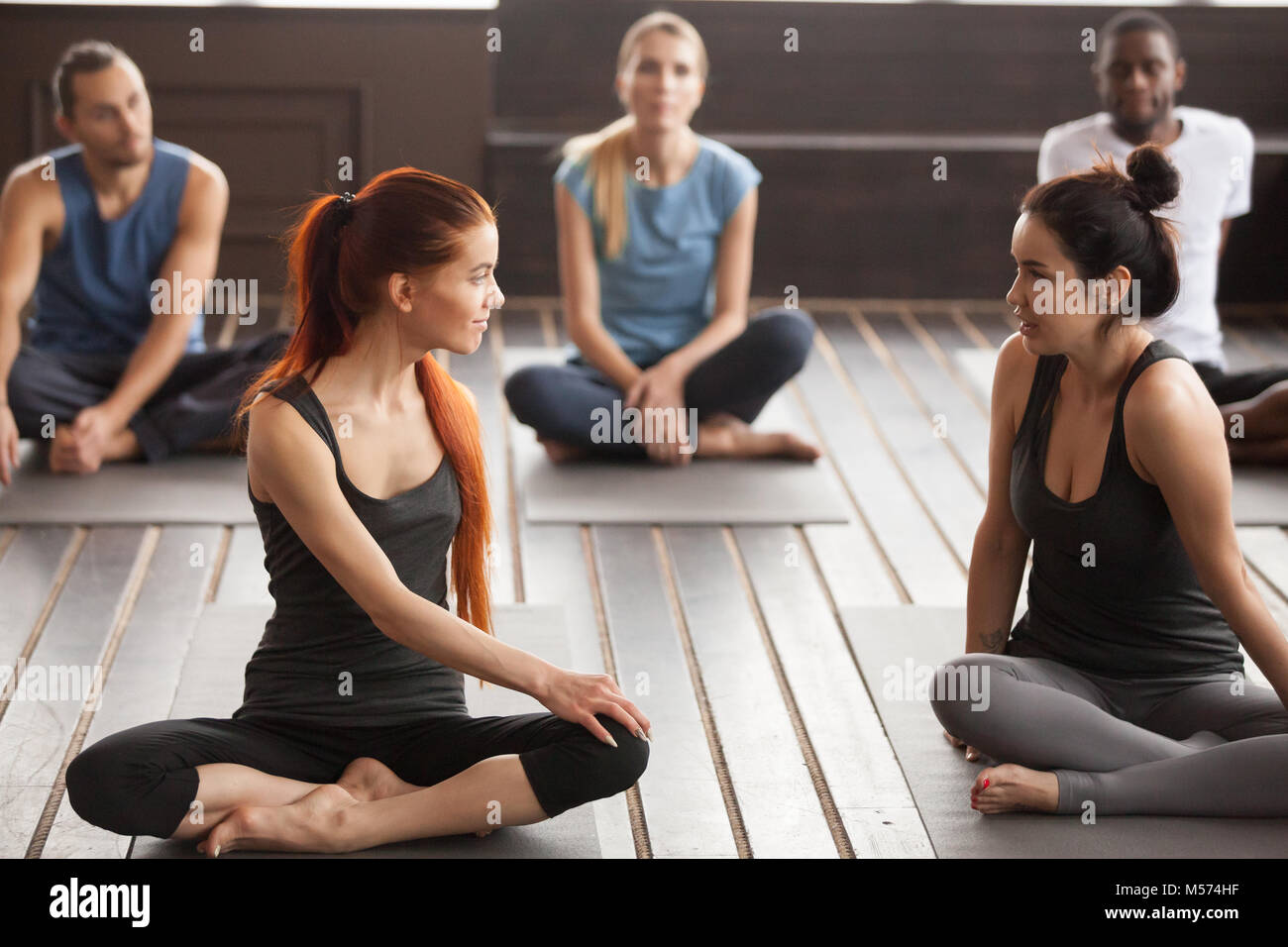 Two young beautiful fit women talking at group yoga training - Stock Image