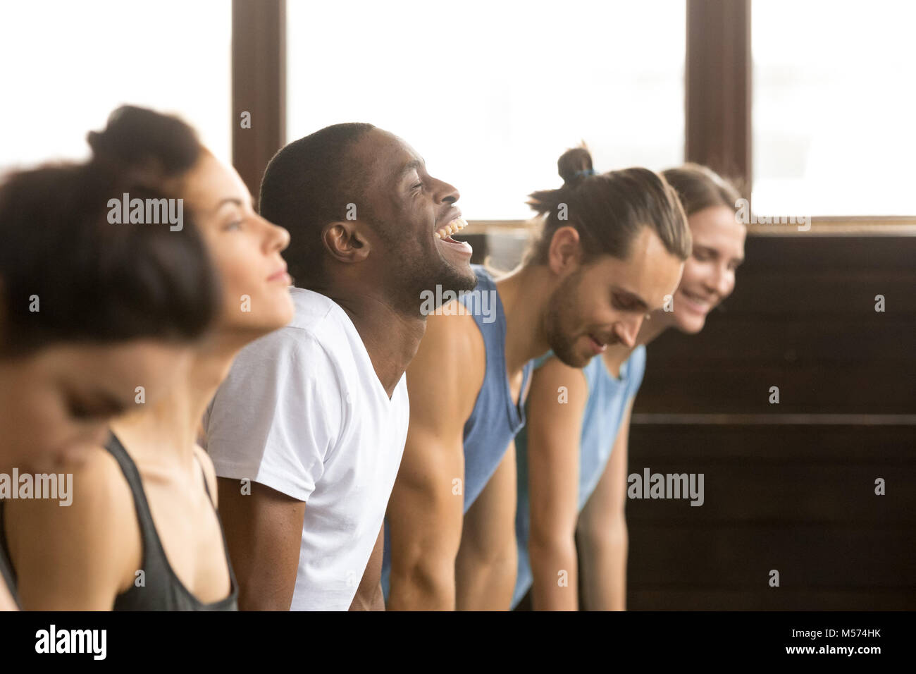 African man laughing doing yoga or plank at group training - Stock Image