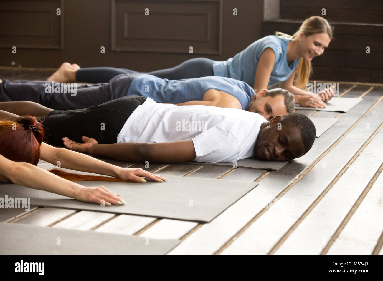 Tired diverse people relaxing on mats after yoga stretching trai - Stock Image