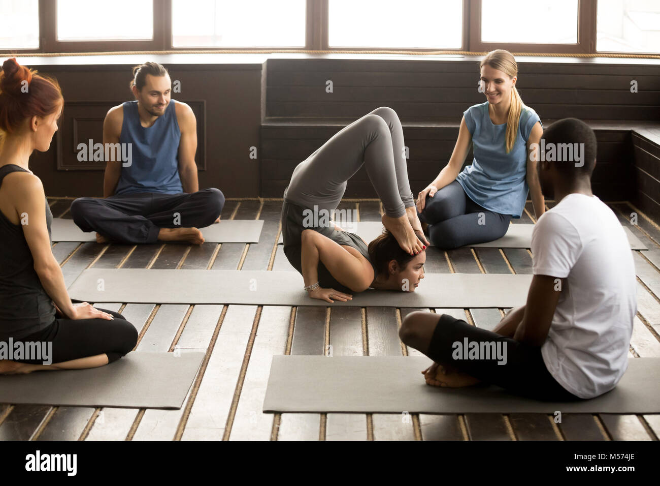 Multiracial people looking at instructor performing yoga pose at - Stock Image