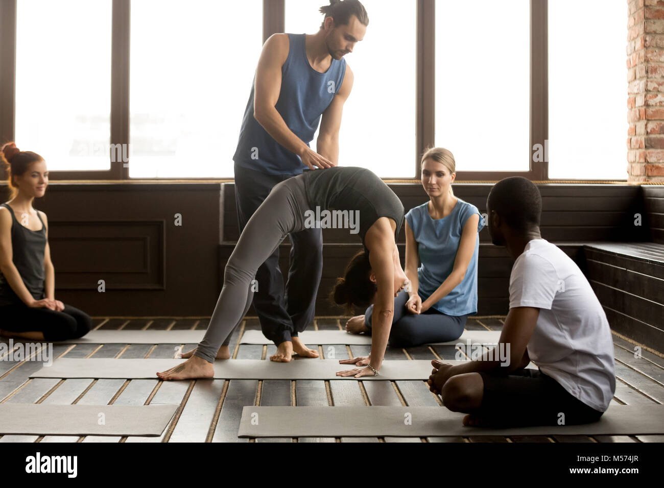Male teacher assisting woman doing yoga bridge exercise on mat - Stock Image