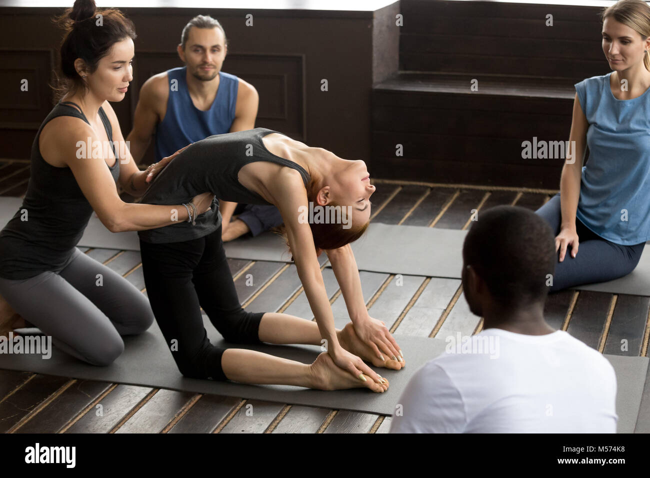 Teacher assisting woman learning new yoga pose at group training - Stock Image