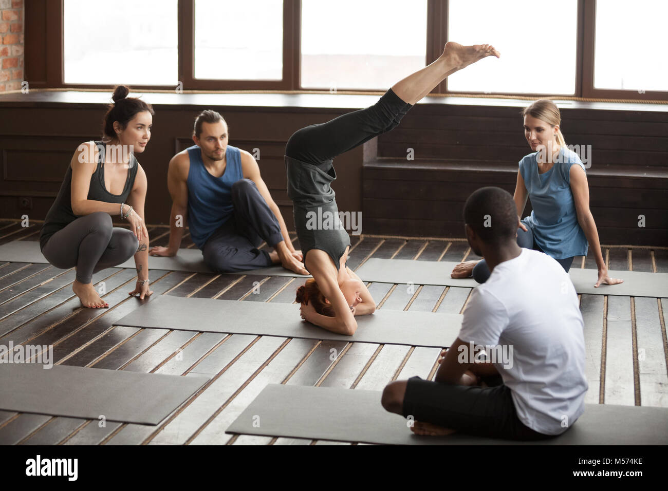 Woman standing on head practicing yoga at group training class - Stock Image