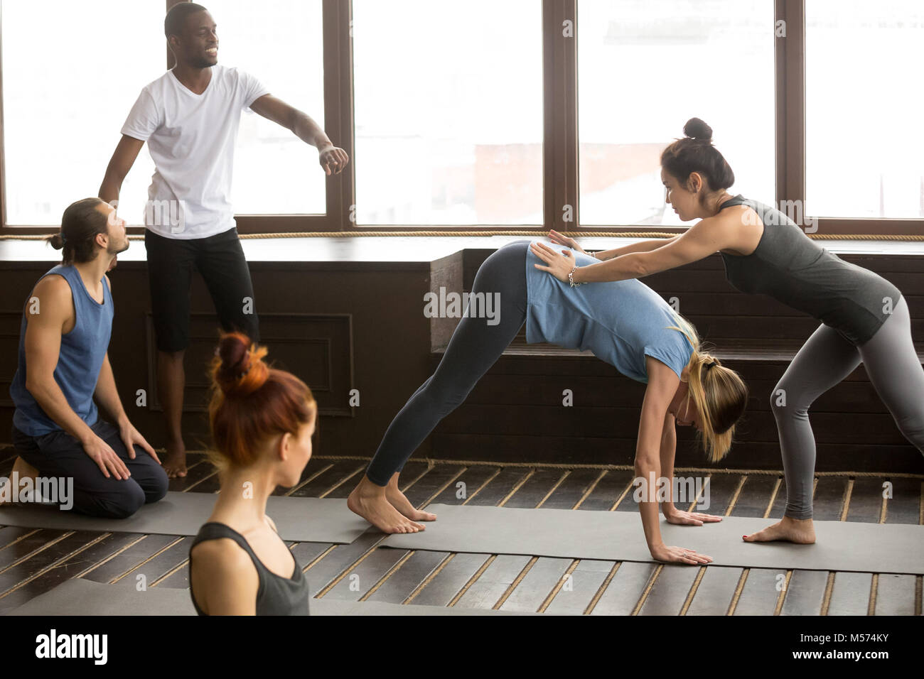 Yoga teacher assisting woman doing downward facing dog stretchin - Stock Image