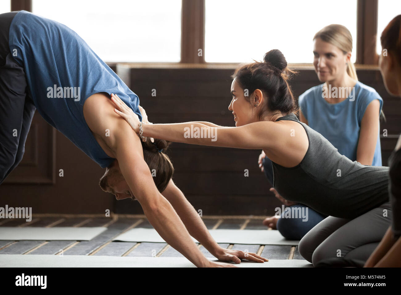 Yoga teacher helping man to stretch holding hands on shoulders - Stock Image