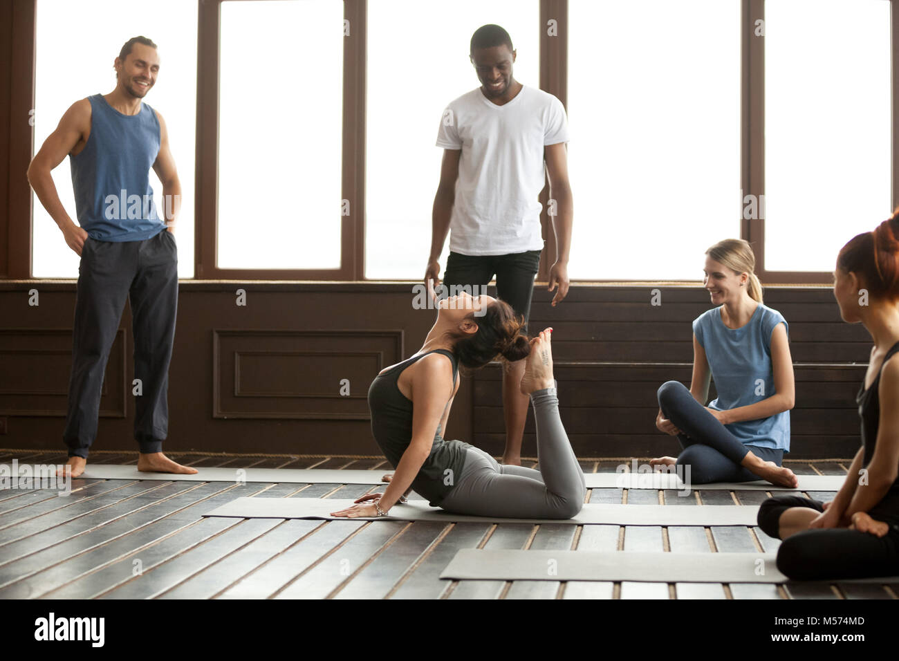 Yoga instructor performing raja bhudjangasana advanced exercise  - Stock Image