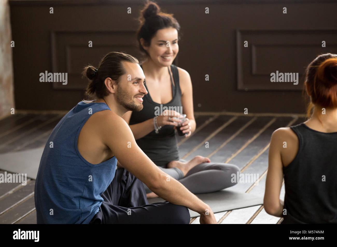 Smiling mindful yogi man sitting on mat at group training - Stock Image