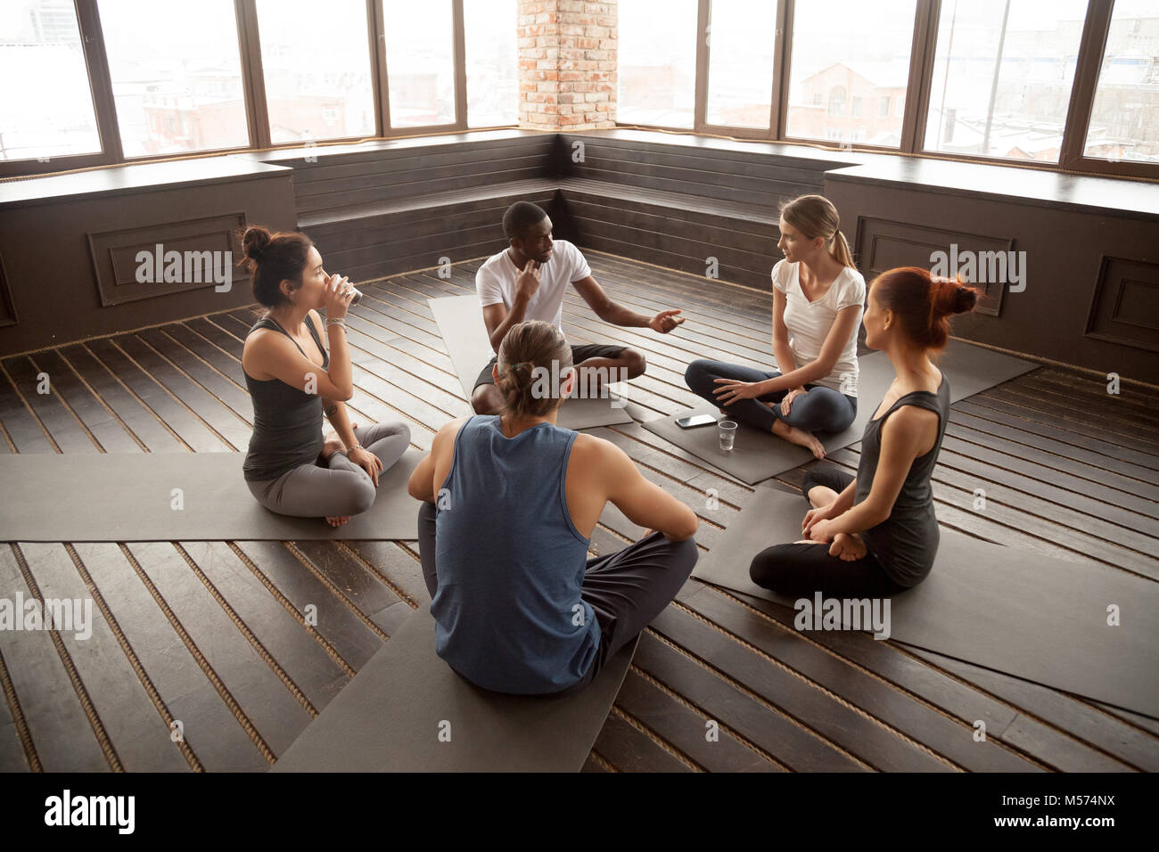 African-american yoga instructor talking to diverse group sittin - Stock Image