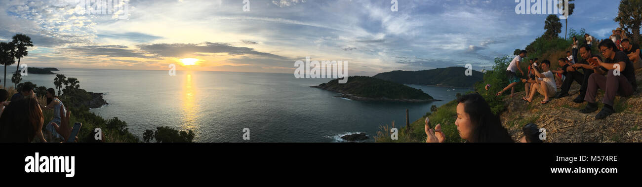 Tourists watching the sunset at Promthep Cape Phuket and taking photos with cameras and smartphones - Stock Image