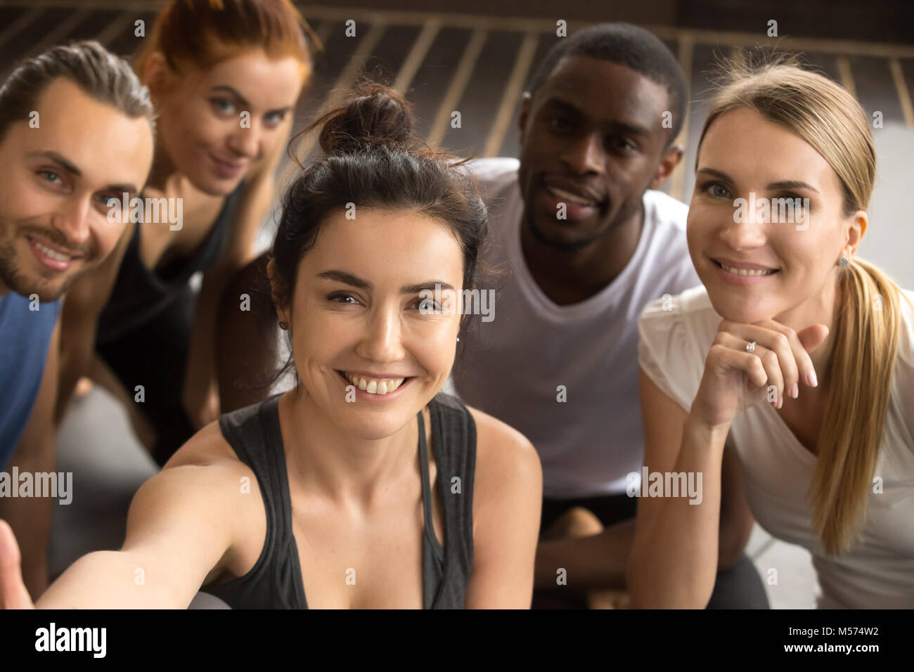 Sporty multiracial friends taking group selfie holding looking a - Stock Image