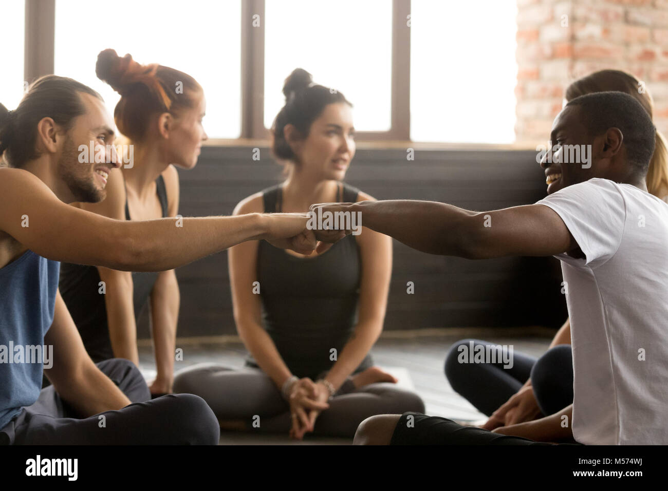 African american and caucasian men fist bumping at group trainin - Stock Image