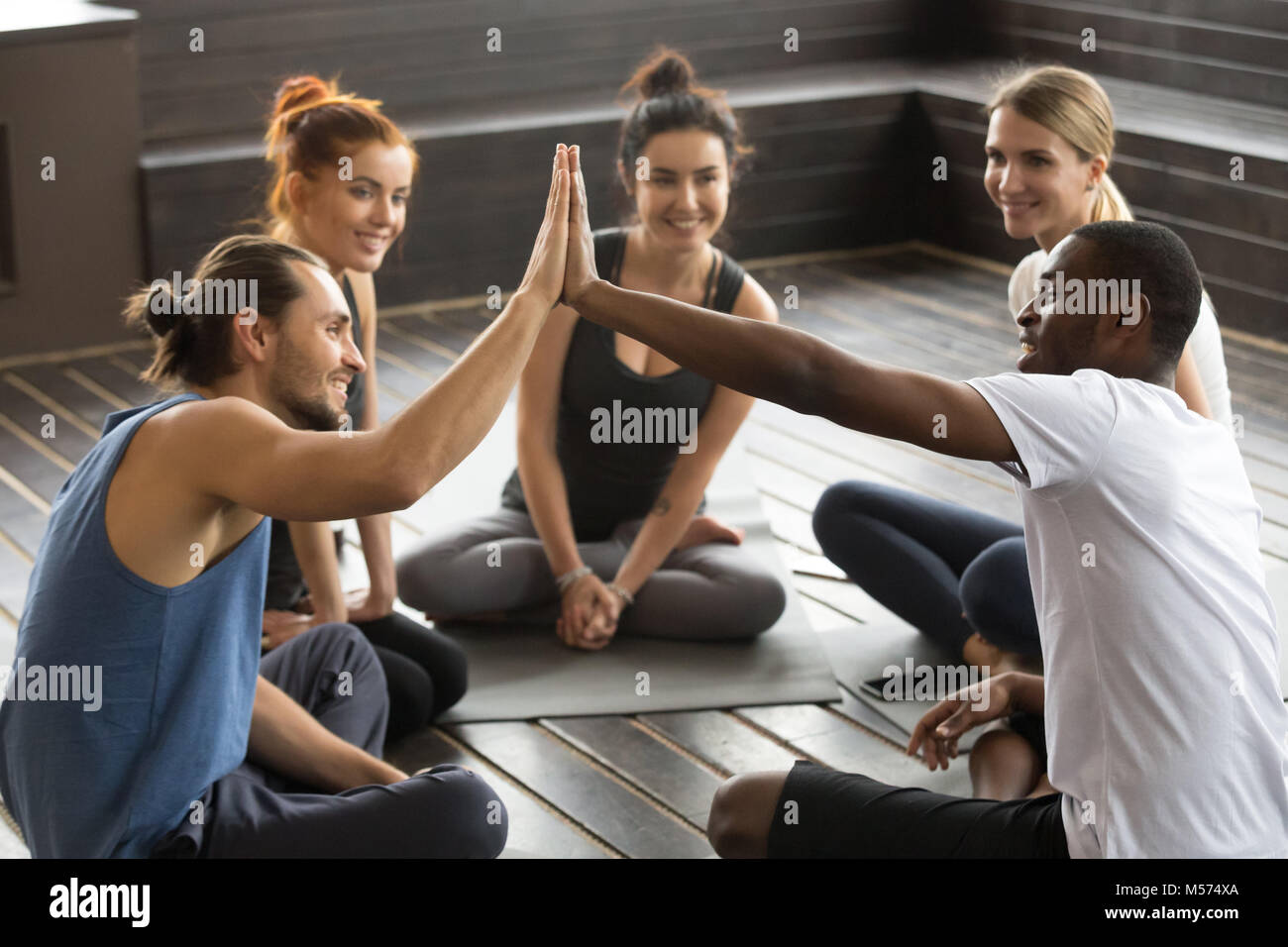 Smiling diverse yoga team members giving high-five at group trai - Stock Image
