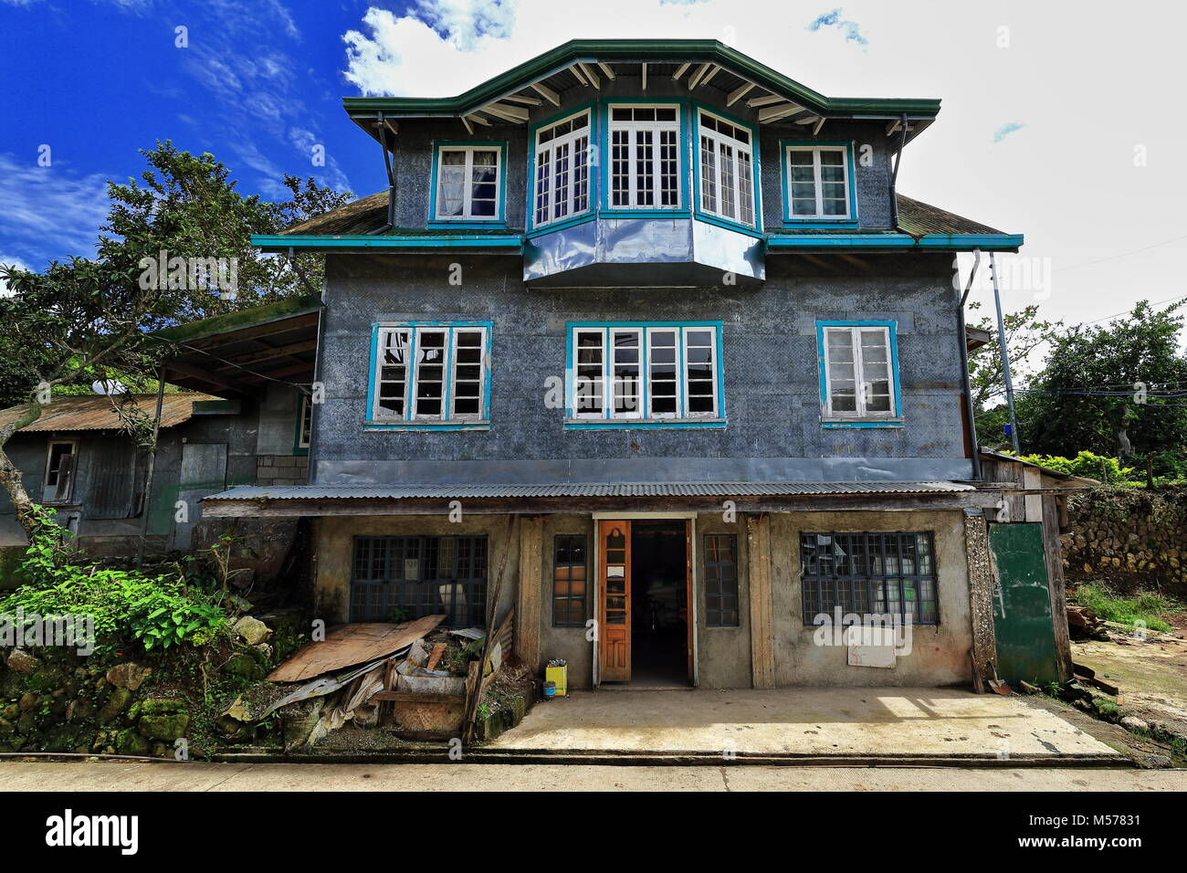 Filipino vernacular architecture-three storey grey cottage with tin roof and feed store on the ground floor by the - Stock Image