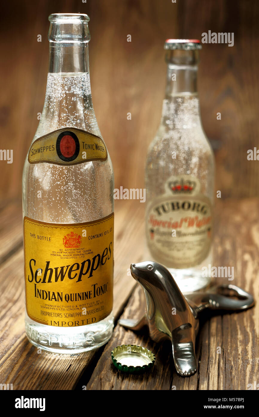 Schweppes - old, pre-war bottles with a refreshing drink and a historic seal-shaped opener - Stock Image