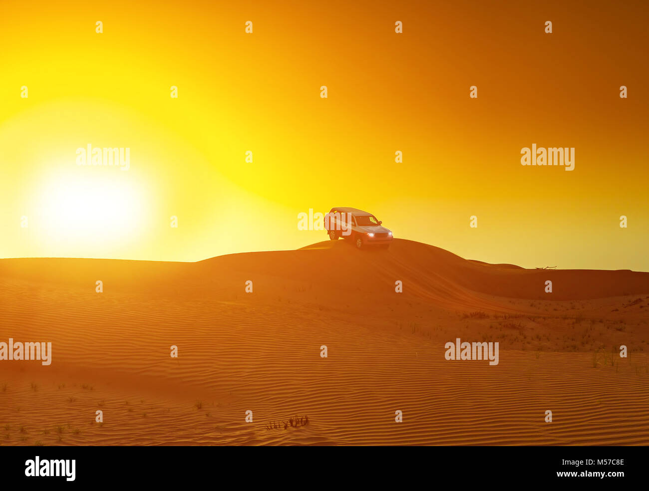 Offroad truck or suv riding dune in arabian desert at sunset. Offroad has been modified to be unrecognized. - Stock Image