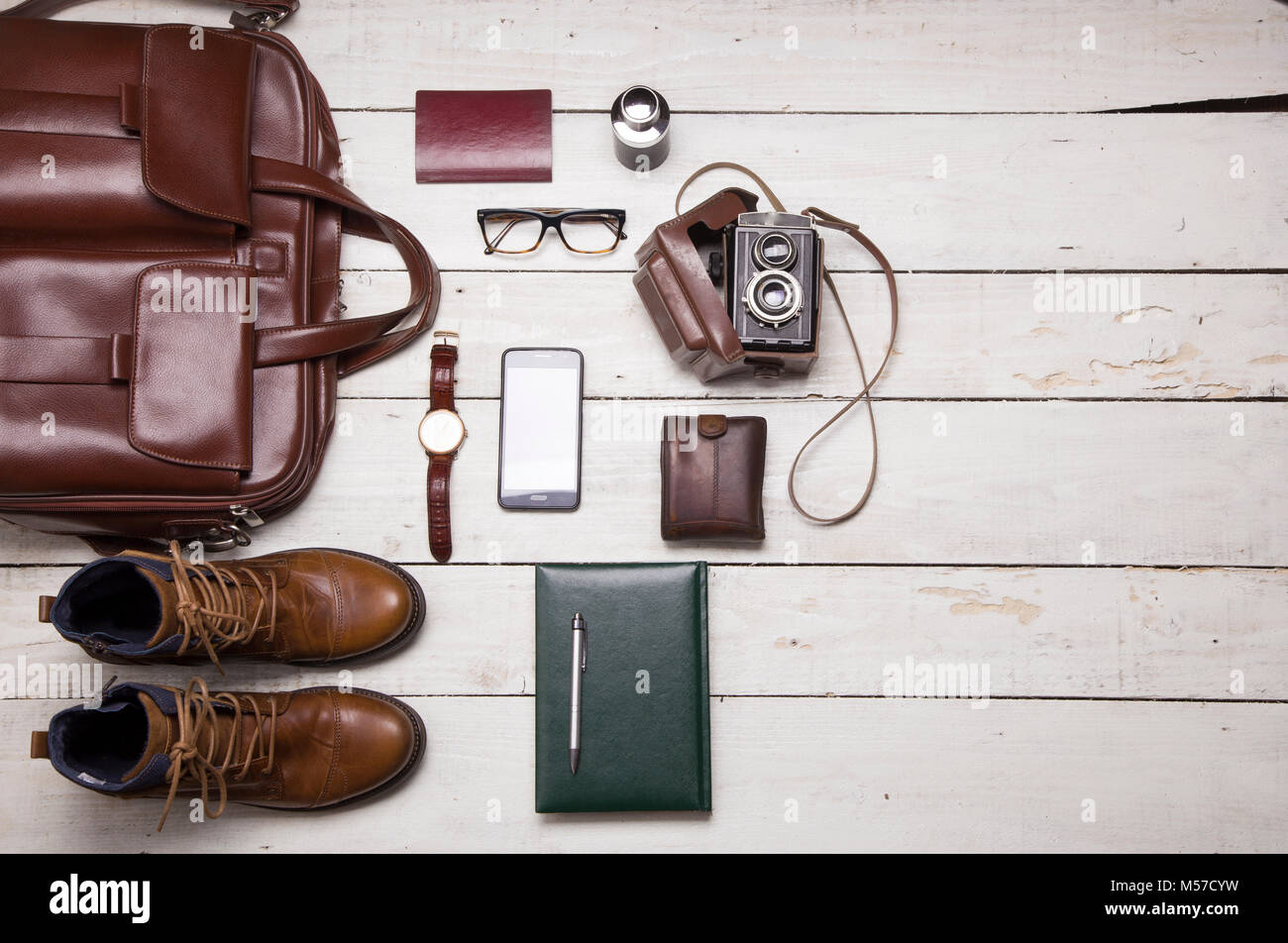 Still life with Men's casual outfits with leather accessories on brown wooden background, beauty and fashion, travel Stock Photo