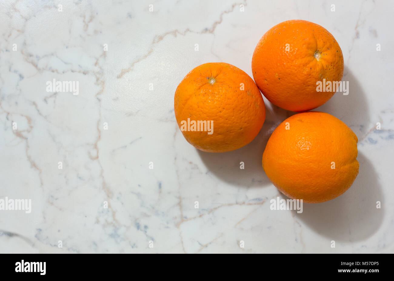 Three oranges on a white marble-like background - Stock Image
