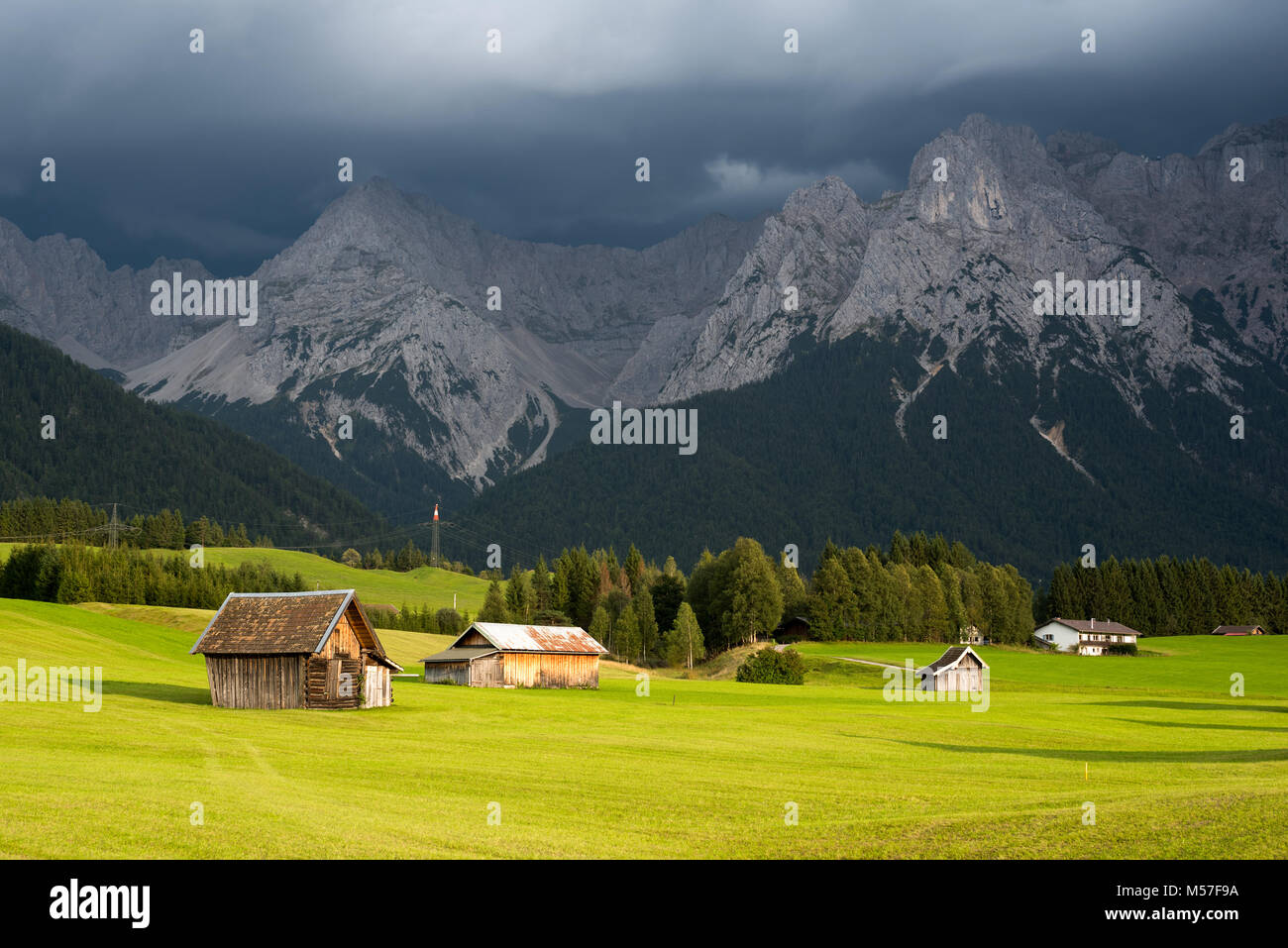 Country houses on green grass against mountain under low cloud - Stock Image