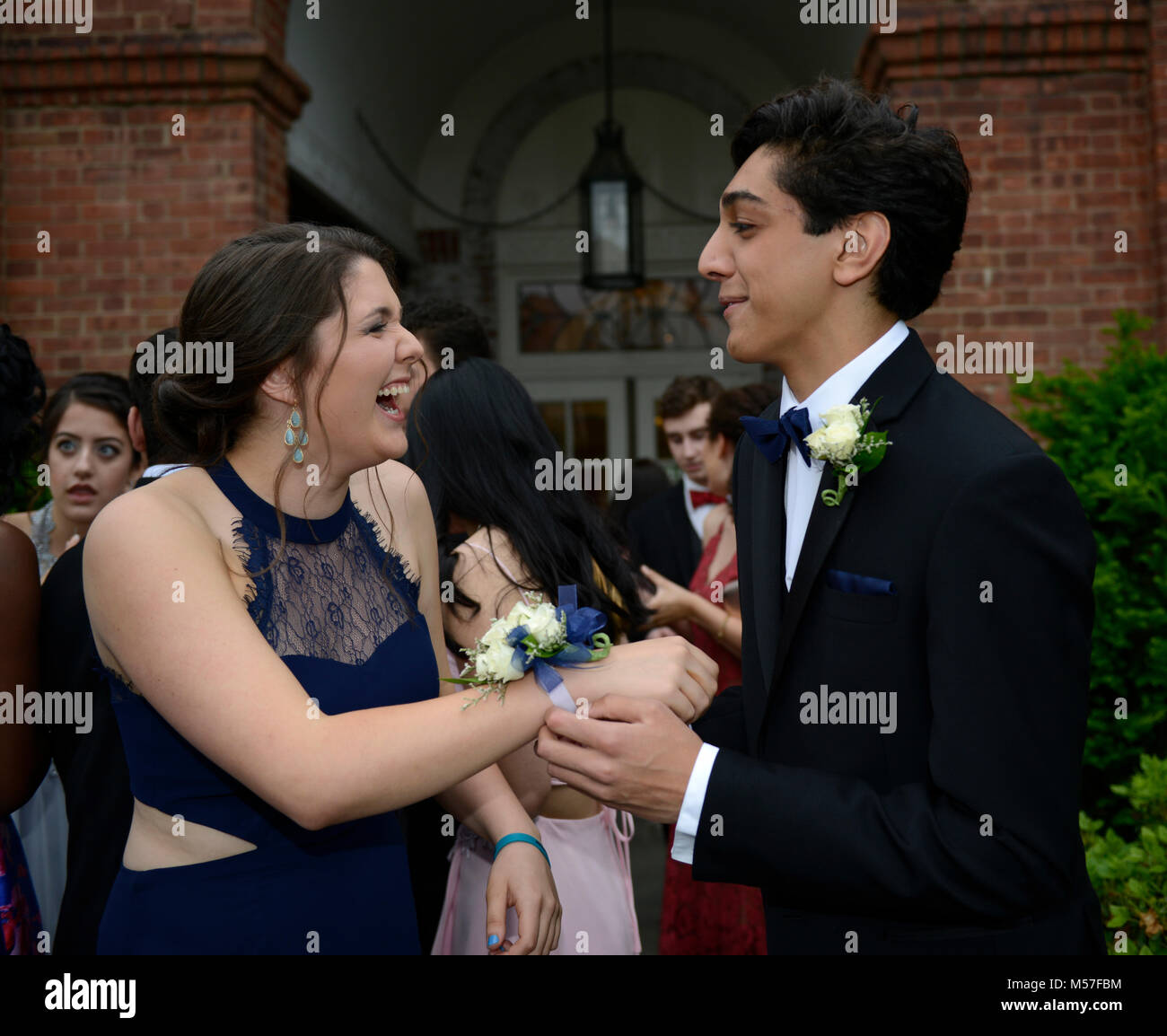 17 yr old high school juniors who just put on their boutonniere and wrist bouquet for prom.  He is Indian-American - Stock Image